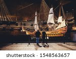 People in front of model of Vasa, viking ship. The ship itself in the background