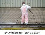 Worker cleaning with high-pressure cleaner railways in port - stock photo