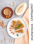 Small photo of Traditional turkish candy cezerye made from caramelised melon, roasted walnuts, hazelnuts, pistachios on white ceramic plate and a cup of coffee on a gray concrete background. top view, flat lay, clo