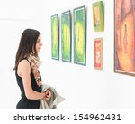 Stock photo side view of young caucasian woman standing in an art gallery in front of colorful framed paintings 154962431