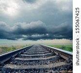 railroad closeup to horizon in rainy clouds - stock photo