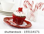 Christmas decorated chocolate cupcake with vanilla frosting and candy-canes.               - stock photo