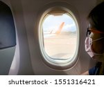 Small photo of Sick woman wear face mask sit on passenger economy seat near cabin window in airplane. Passenger in departure flight plane at the airport. Novel coronavirus (2019-nCoV) infection or Wuhan coronavirus
