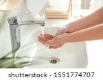 Young Woman Washing Hands With...