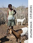 Small photo of African woman with braids dressed in colorful clothes standing in the kraal