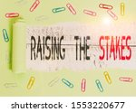 Word writing text Raising The Stakes. Business concept for Increase the Bid or Value Outdo current bet or risk Paper clip and torn cardboard placed above a wooden classic table backdrop. - stock photo