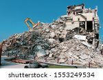 Demolishing a building in the city. Excavator is demolishing concrete walls.