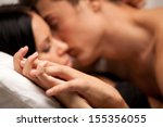 Stock photo young lovers kissing on the couch focused on hand 155356055