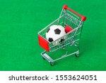 Soccer ball in shopping cart on green foorbal field