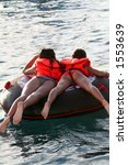Small photo of two girls on a towable buoy