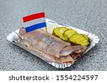 Stock photo traditional dutch appetizer of herring pickles and onions on a paper plate in an outdoor cafe 1554224597