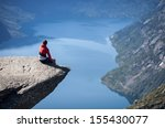 man sitting on trolltunga in... | Shutterstock . vector #155430077