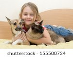 Stock photo girl with pets on a bed of yellow color 155500724