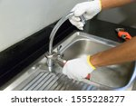 Plumber fixing white sink pipe with adjustable wrench. - stock photo