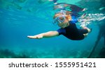 Small photo of Happy little kid in snorkeling mask and wetsuit jump and dive underwater in coral reef sea lagoon. Family travel lifestyle in summer adventure camp. Swimming activities on beach vacation with child.