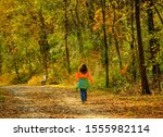 Small photo of Slightly overweight woman in bright clothes walking briskly on trail in park in fall; Missouri, Midwest