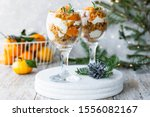 Small photo of Citrus trifle with carrot biscuit and fresh tangerines in a glass. Christmas portioned dessert on the festive table.