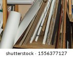 Small photo of creative clutter on the shelves in your art workshop. papers, folders, sheets, rolls - all the same, everything is mixed up