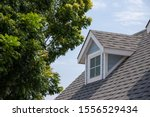 Small photo of Roof shingles with garret house on top of the house among a lot of trees. dark asphalt tiles on the roof background