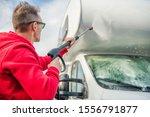 Caucasian Men in His 30s Cleaning His Camper Van After Season. RV Motorhome Pressure Washing.  - stock photo