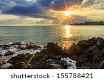 Morning sea landscape with rocky coast, menacing skies, reflections and the rays of the rising sun - stock photo