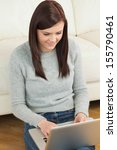 smiling brunette using a laptop ... | Shutterstock . vector #155790461
