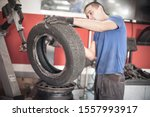 Car master mechanic vulcanizer repairing tire on automatic rubber repair vulcanizer machine in auto vulcanizing and vehicle service workshop - stock photo