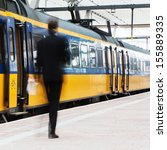 unrecognizable businessman arriving with a train at the station and walking on the platform  - stock photo