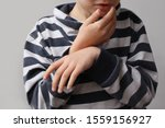 Small photo of boy, a child in a striped jumper holds on to the lower jaw, the second hand hung limp from suffering, toothache concept