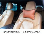 The seats in the car are made of brown leather with pillows for the neck and rest during long trips and travels. - stock photo
