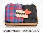 Small photo of Donation concept. Donation box with donation clothes on a white background. Charity. Helping needy people.