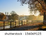 embankment of the old town strewn with foliage and filled with light on autumn morning - stock photo