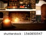 Christmas candles with fire on top of board.Free space for your decoration.Xmas time in home of the hunter's house.Big retro fireplace and american hunter rifles on a stand.Copy space and mood photo. - stock photo