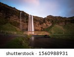 Seljalandsfoss waterfall, flowing river, and bridge long exposure during a sunset in Iceland off the ring road. The waterfall is one of the most amazing places in the world and should be on every list - stock photo