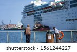 Keelung/Taiwan 11.05.2019 beggar man in port against the backdrop of a huge white cruise ship. homeless man rummaging in a garbage bin on the background of a luxury liner for passengers - stock photo