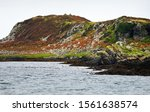 Stormy weather. Panoramic view of the shores, mountains and valleys of Jura island from the water. Cloudy blue sky. Paps of Jura, Inner Hebrides, Scotland, UK
