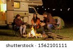 Group of close friends laughing together around camp fire. Retro camper van. Light bulbs in the background. - stock photo
