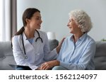 Small photo of Happy young female nurse provide care medical service help support smiling old grandma at homecare medical visit, lady carer doctor give empathy encourage retired patient sit on sofa at home hospital