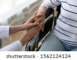 Small photo of Young female nurse caregiver hold hand support disabled handicapped senior adult grandma patient sit on wheelchair, old paralyzed people with disability medical help assistance concept, close up view