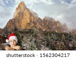 Small photo of Charming boy in a clownish cap of Santa Claus smiles. The first snow. Magnificent panorama of Giau Pass, Dolomite Alps. Concept of Christmas and New Year tourism
