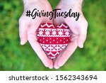 Small photo of Giving Tuesday is a global day of charitable giving after Black Friday shopping day. Charity, give help, donations and support concept with text message sign and red knitted heart in man handful