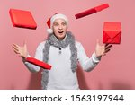 Small photo of Handsome man in a white sweater, Santa hat and trumpery shows magic making Christmas gifts livitate around him.