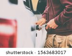 Car theft thief stealing vehicle. Street crime man breaking in automobile to steal. - stock photo