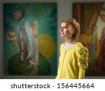 Stock photo side view of beautiful caucasian woman contemplating artworks in an art museum 156445664