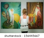 Stock photo rear view of younga caucasian woman stading in an art gallery in front of two large colorful 156445667