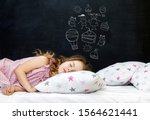 Stock photo charming little girl of preschool age sleeps in bed on a pillow with stars time to sleep drawing 1564621441
