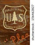 Distressed wooden sign with carved US Forest Service and Department of Agriculture logo at a camp site.