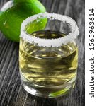 Small photo of one shot, one shot of strong alcohol with tequila and salt, lime green in the background, still life alcoholic on a dark wooden background.