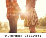 Stock photo young couple in love walking in the autumn park holding hands looking in the sunset 156614561
