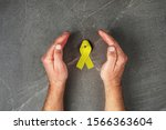 Small photo of golden ribbon childhood symbol of the fight against cancer in children in hands on gray background. concept of helping patients with sarcoma and bladder cancer.